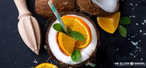 Kokosnoot gevuld met drank, sinaasappel en een rietje