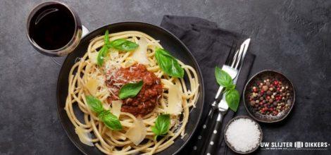 Een bord met pasta en een glas wijn